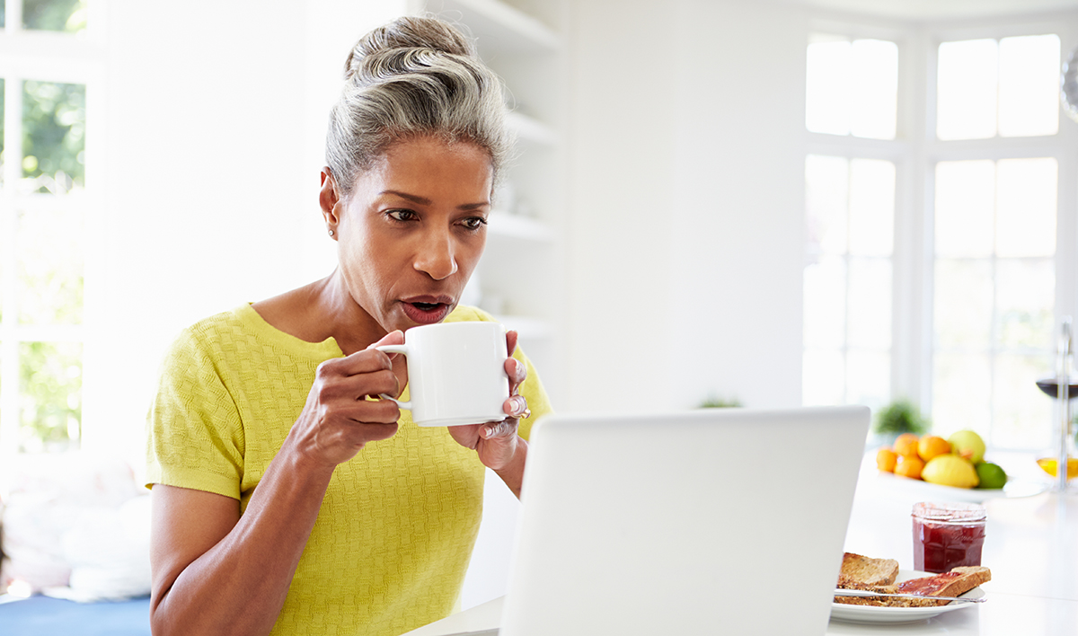 Woman drinking a cup of coffee and looking through emails.